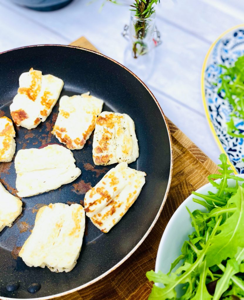 halloumi being fried in a pan. bowl of salad alongside pan