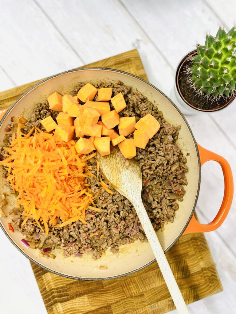 adding grated carrot and sweet potato chunks to spiced minced beef for mexican cottage pie filling