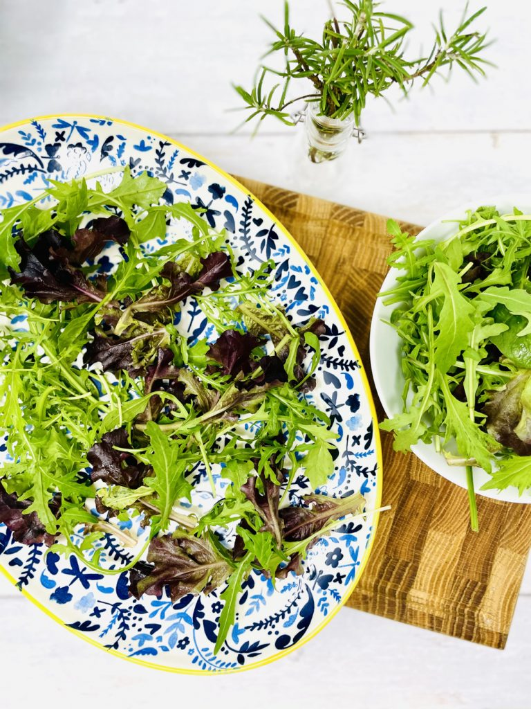 blue and yellow floral plate with salad leaves, ready to be topped with lentil salad