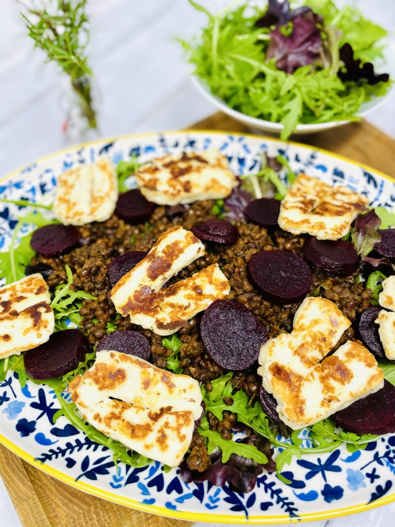 warm lentil salad with halloumi cheese made using merchant gourmet lentils served on a blue and yellow floral plate on a wooden board