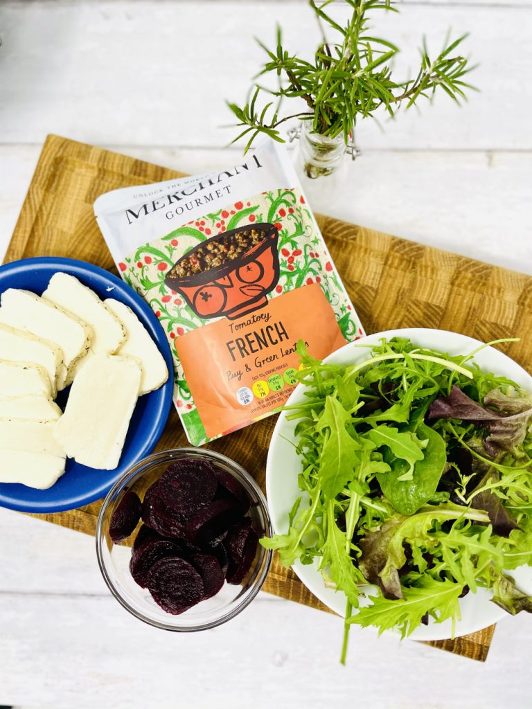 warm lentil salad ingredients on a wooden board - merchant gourmet tomatoey French puy and green lentils, sliced halloumi cheese, sliced beetroot and a bowl of mixed rocket and salad leaves