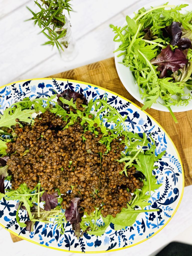blue and yellow floral plate with salad leaves, warm merchant gourmet lentils
