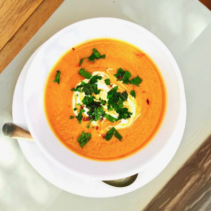 moroccan vegetable soup served with a swirl of soured cream, chilli flakes and chopped flat leaf parsley