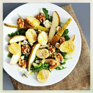 pear and blue cheese salad recipe with walnuts and croutons drizzled in olive oil, served on a white plate on a piece of hessian sacking