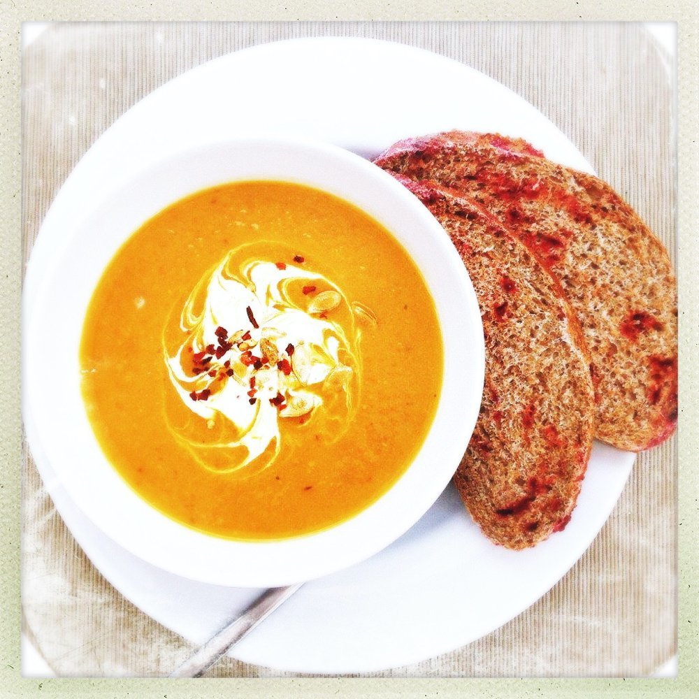 bowl full of homemade roasted butternut squash soup served with a swirl of creme fraiche and sprinkle of chilli flakes. On the side is some delicious beetroot bread ready for dunking
