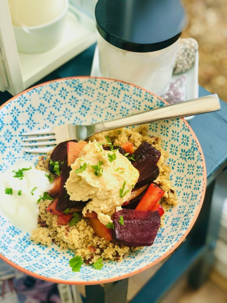 roasted root vegetable couscous bowl - Moroccan couscous topped with roasted carrots, sweet potatoes and beetroot topped with spicy hummus and greek yogurt scattered with coriander