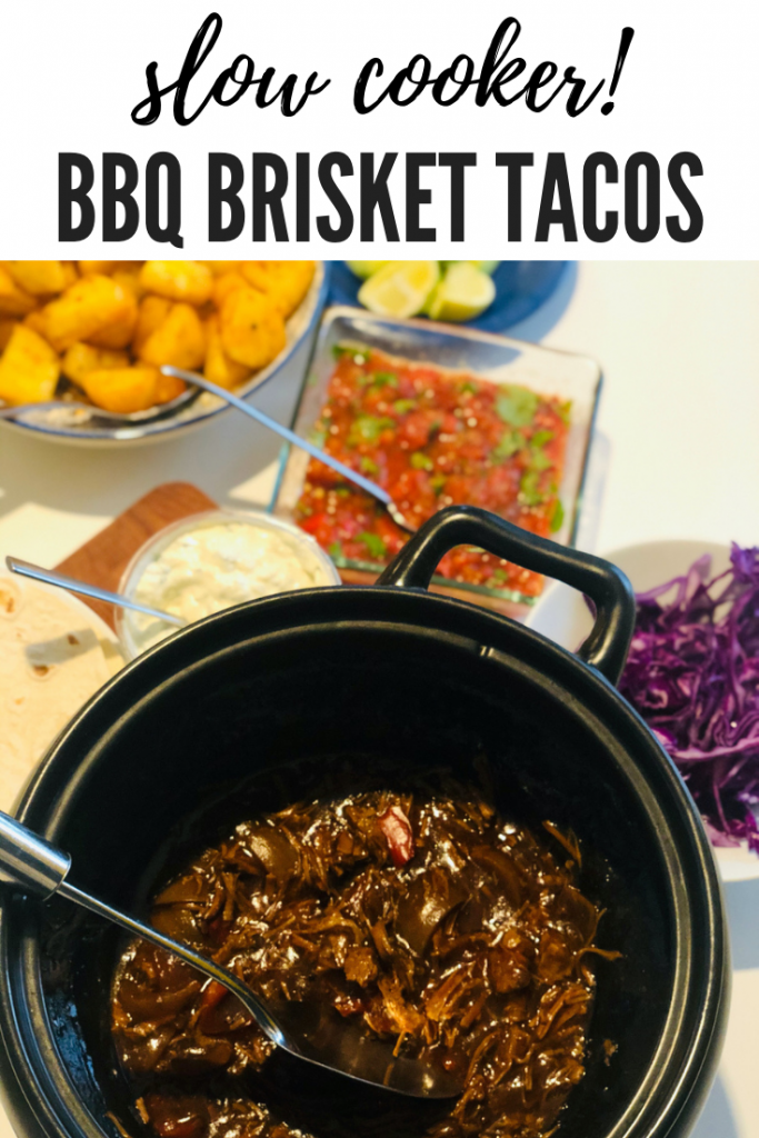 "slow cooker brisket tacos - slow cooker filled with pulled slow cooker BBQ brisket, served alongside bowls of toppings including shredded red cabbage, homemade Mexican roasted tomato salsa, spicy roast potatoes and sour cream dip. Text overlay ""slow cooker BBQ brisket tacos"""