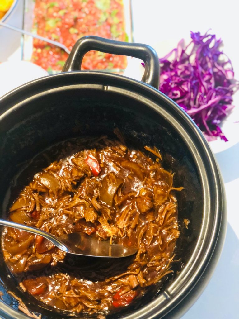 slow cooker brisket tacos - slow cooker filled with pulled slow cooker BBQ brisket, served alongside bowls of toppings including shredded red cabbage, homemade Mexican roasted tomato salsa, spicy roast potatoes and sour cream dip