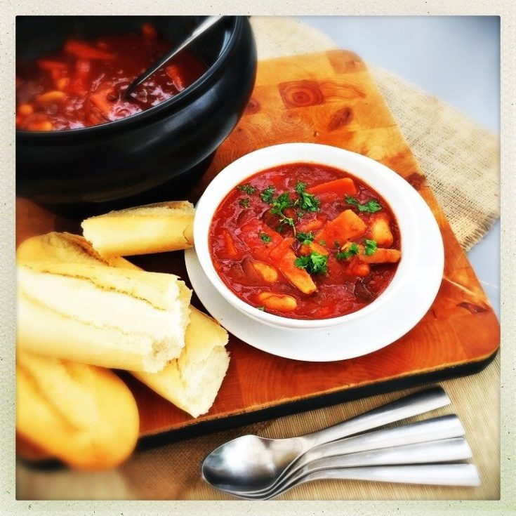 beef and vegetable stew served from the black crockpot pan into white bowls, pile of french baguettes at the side of the bowl on a wooden board