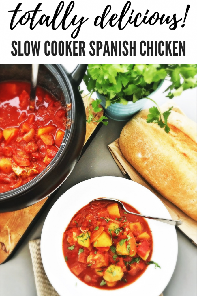 """spanish chicken stew in the slow cooker pan - some served in a white bowl with chopped flat leaf parsley scattered over the top. Loaf of bread and pot of herbs are by the side. Text overlay """"Totally delicious slow cooker spanish chicken"""""""