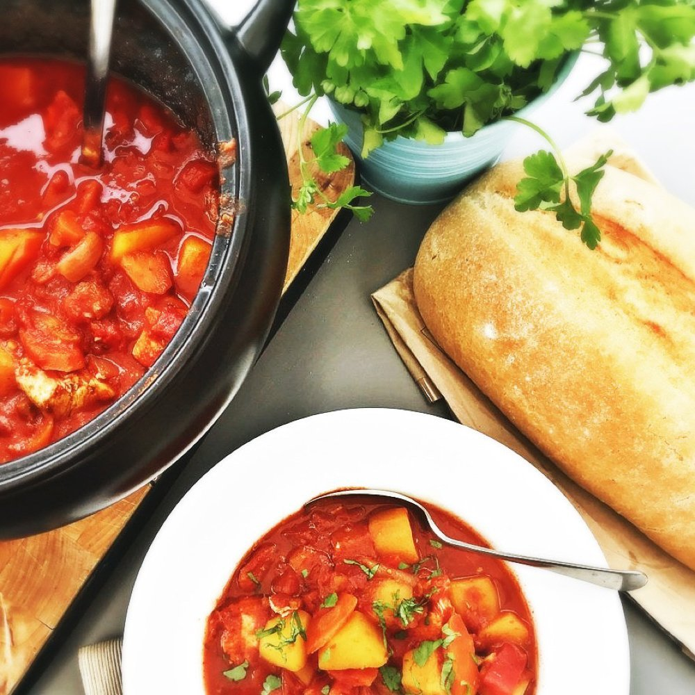 spanish chicken stew in the slow cooker pan - some served in a white bowl with chopped flat leaf parsley scattered over the top. Loaf of bread and pot of herbs are by the side.
