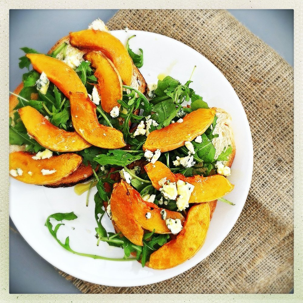 butternut squash bruschetta with rocket and blue cheese served on a white plate resting on a hessian sack