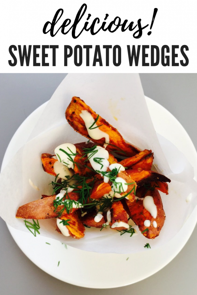 "a paper cone of oven baked sweet potato wedges with lemon and herb mayonnaise drizzled over them and chopped dill scattered over. Text overlay ""delicious sweet potato wedges"""