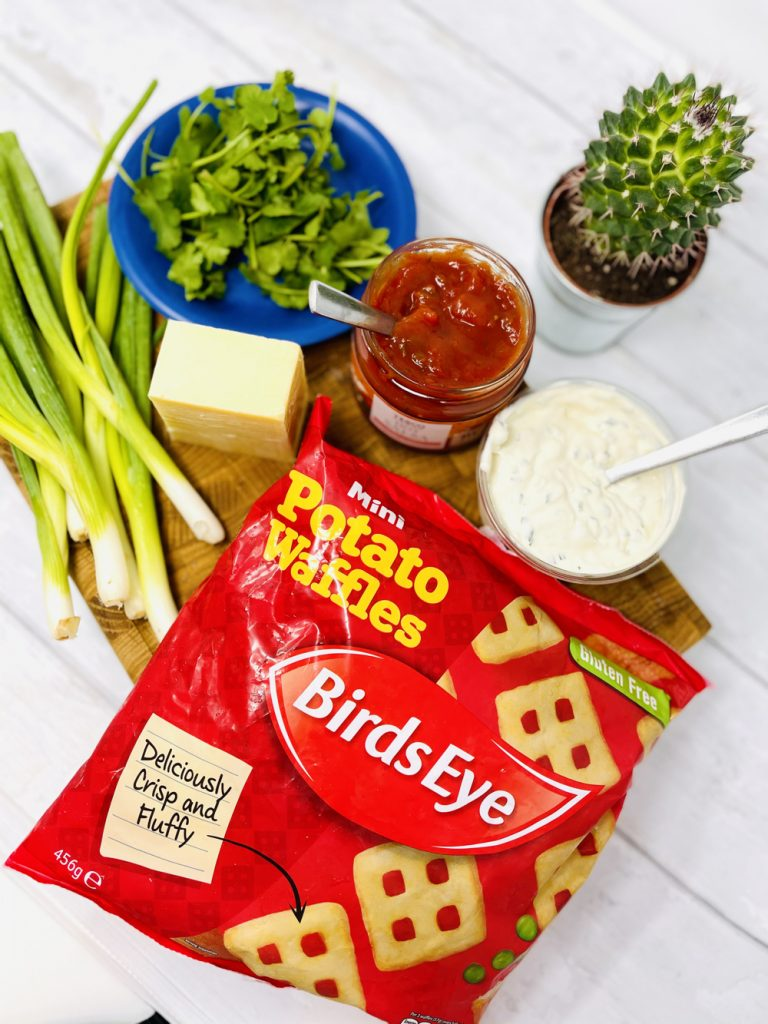 potato waffle nacho ingredients laid out on a wooden board - bag of mini Birds Eye potato waffles, bunch of spring onions, 150g cheddar cheese, handful of chopped coriander, tub of tomato salsa, tub of soured cream and herb dip