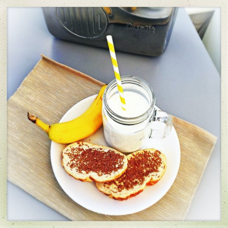 Dutch chocolate sprinkle sandwiches - on white bread served on a plate with a banana and glass of milk with yellow and white striped paper straw