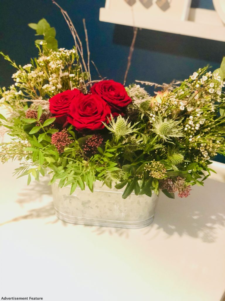 Moonpig Christmas flowers arranged as a festive table centrepiece. Includes red roses, thistle and other whimsical flowers