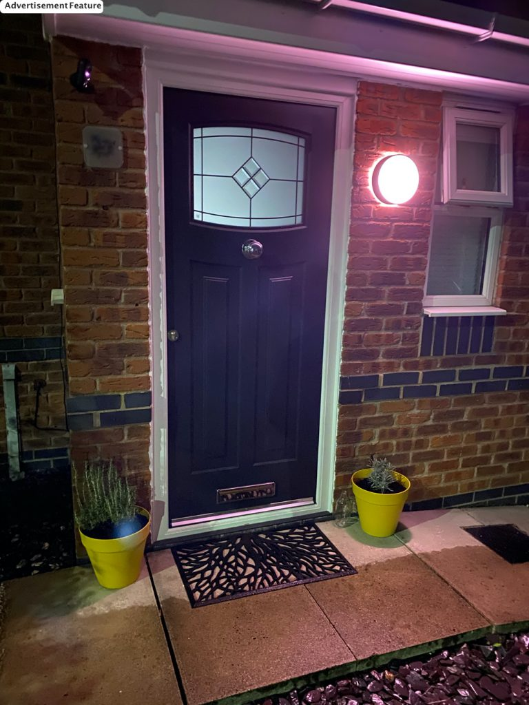 Philips Hue Daylo Outdoor Wall Light lit with pink light next to a grey 1930s style rock door with yellow planters by the door