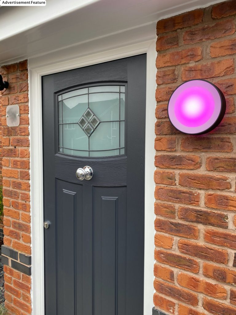 Philips Hue Daylo Outdoor Wall Light lit with pink light next to a grey 1930s style rock door