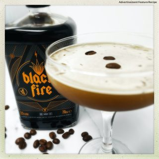 bottle of black fire coffee liqueur next to an espresso martini with coffee beans floating on the surface