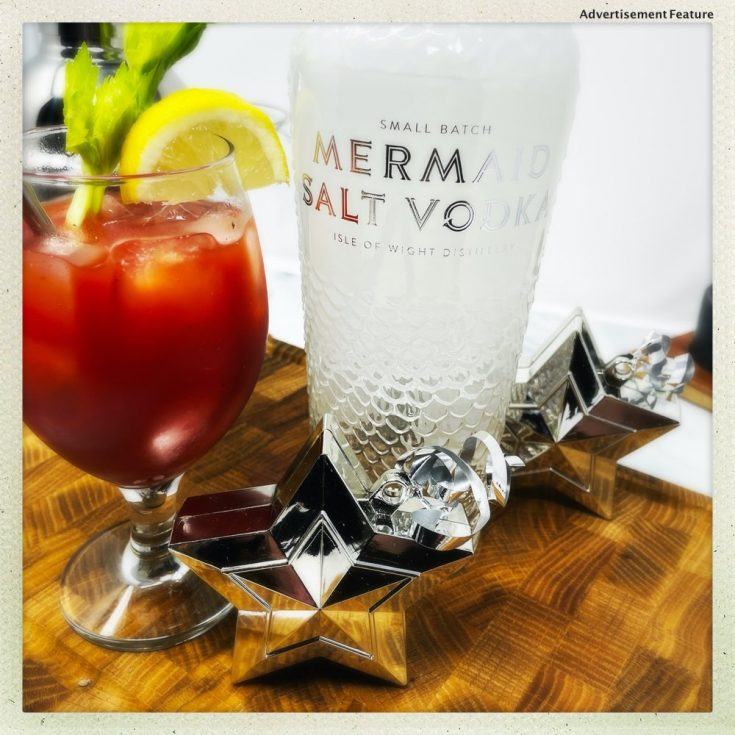Bloody Mary cocktail garnished with celery and lemon wedge served in glass next to a bottle of Mermaid Salt Vodka