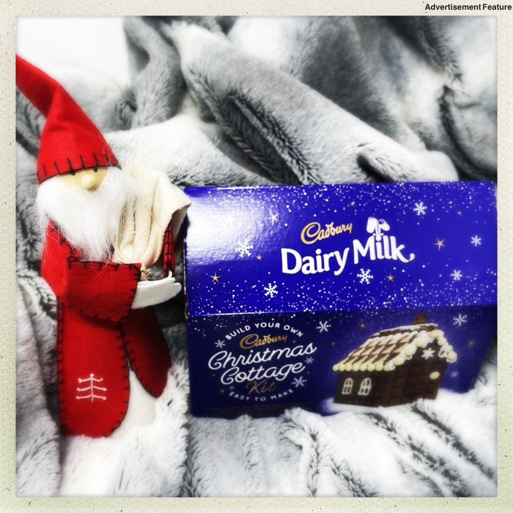 Cadburys chocolate Christmas cottage in a box next to a Nordic santa gnome
