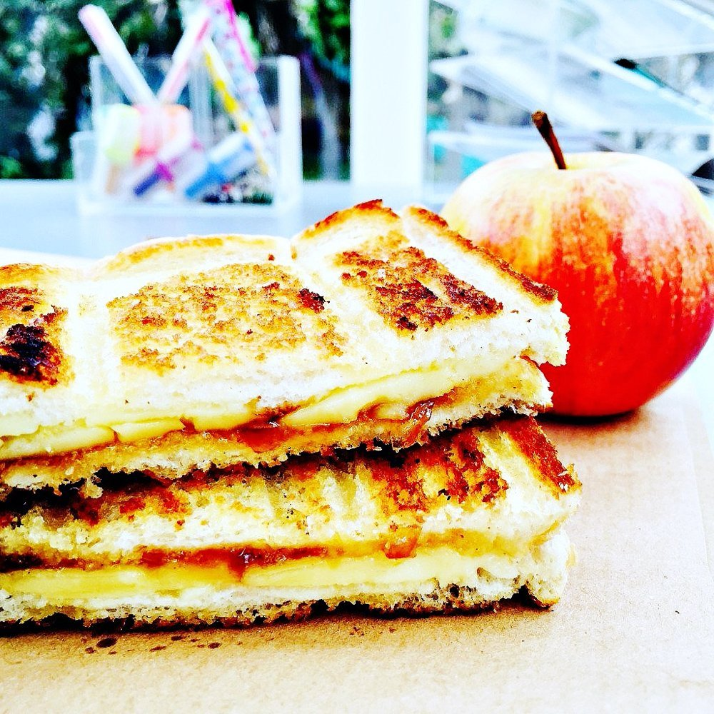 cheese and chutney toasties served on brown paper alongside a red apple