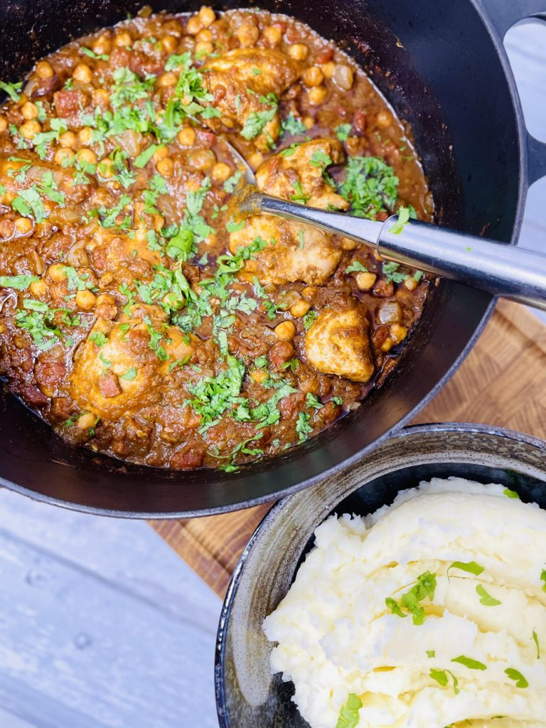 chicken, chorizo and chicken stew in dutch oven served alongside a bowl of creamy mashed potatoes