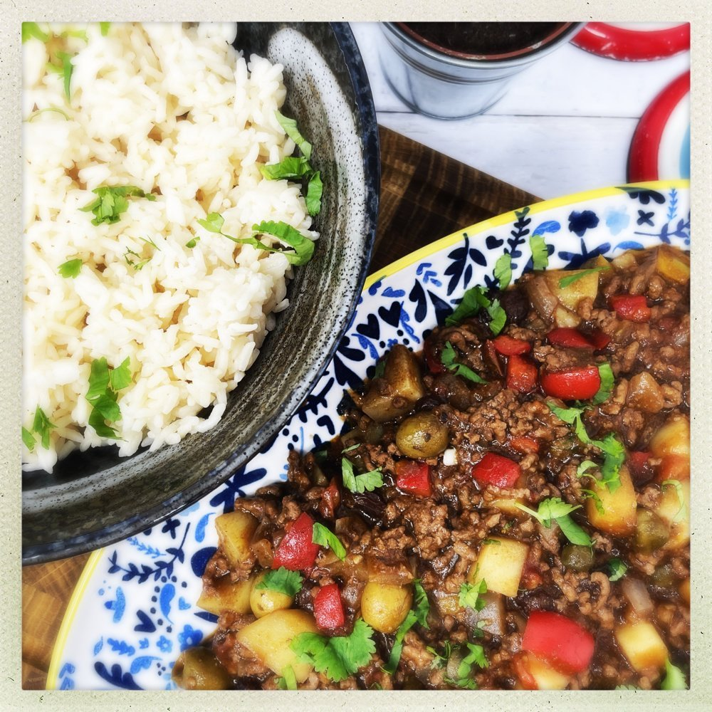 Cuban picadillo on a blue and white floral plate alongside a black bowl filled with white rice.