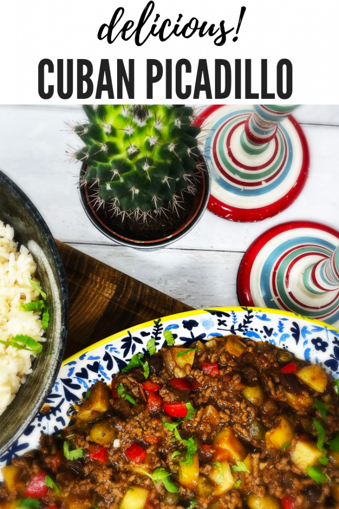 """cuban picadillo with potatoes on a blue and white serving platter alongside a black bowl filled with rice and a cactus next to stripy candlesticks. Text overlay """"delicious cuban picadillo"""""""
