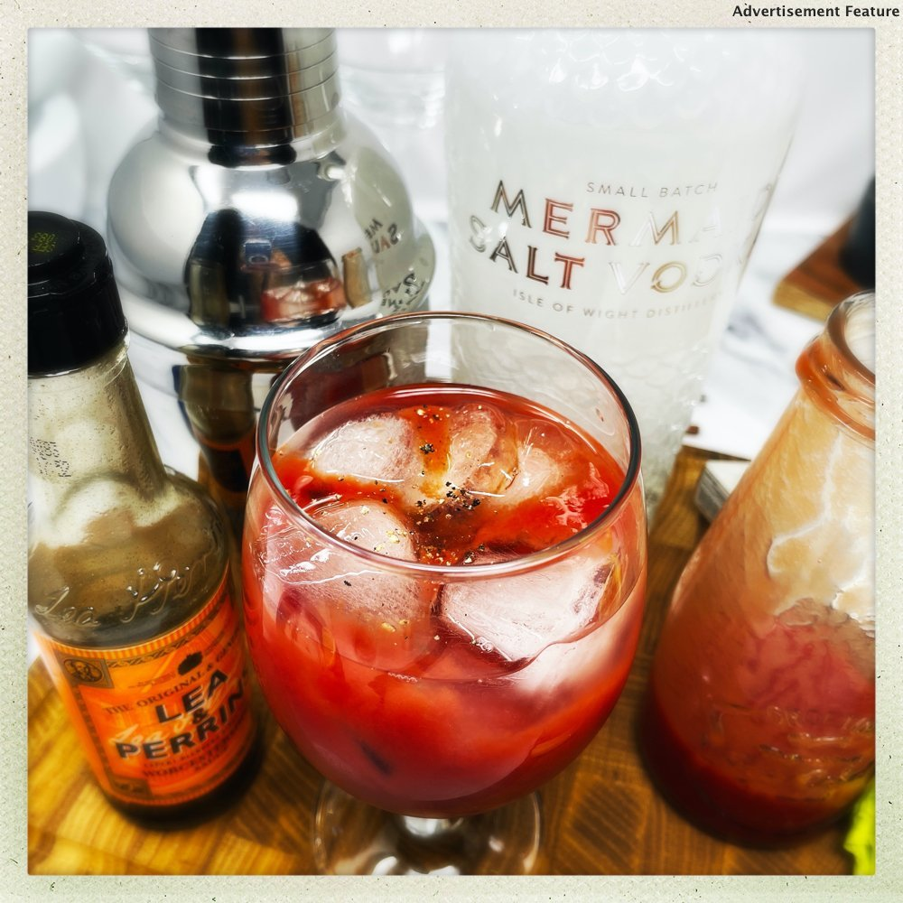 making a bloody mary cocktail with tomato juice and worcestershire sauce bottle by the glass Mermaid Salt vodka bottle in background