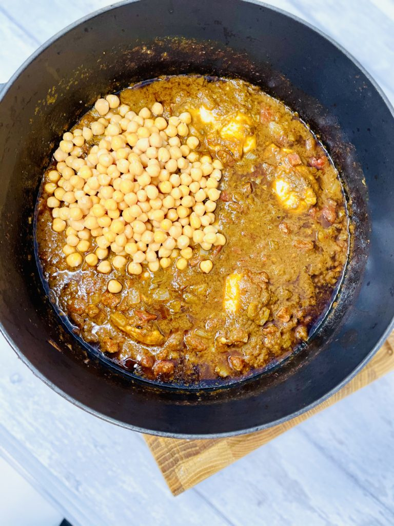chicken and chorizo stew with chickpeas being stirred into the casserole in a dutch oven pan