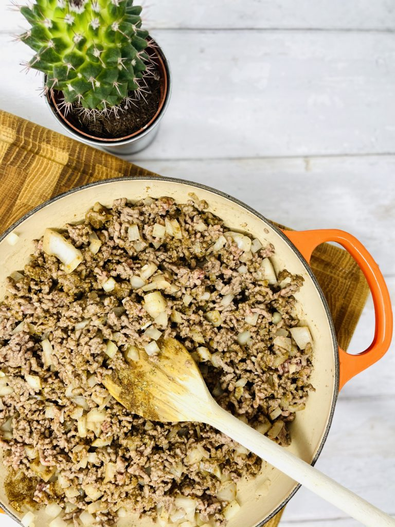 browning mince and onions in a pan being stirred with a wooden spoon