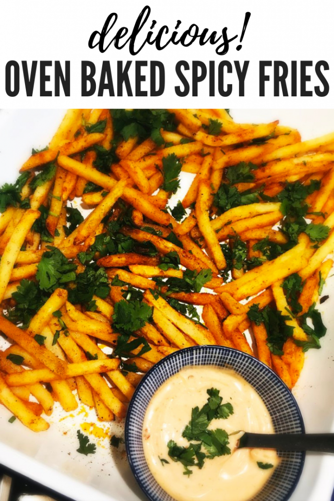 """white enamel roasting tin with homemade spicy oven fries and a small blue and white dish filled with harissa mayonnaise. Text overlay """"delicious oven baked spicy fries"""""""