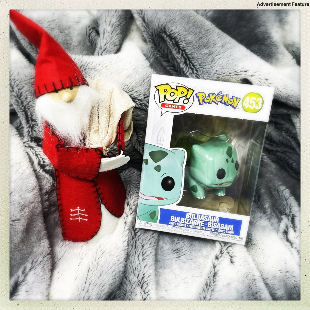 Pokemon Bulbasaur toy in a box next to a Nordic Gnome dressed as Father Christmas