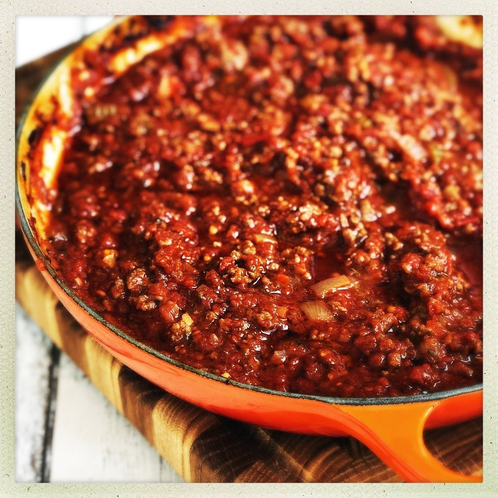 oven baked bolognese sauce in an enamel pan, stood on a wooden chopping board