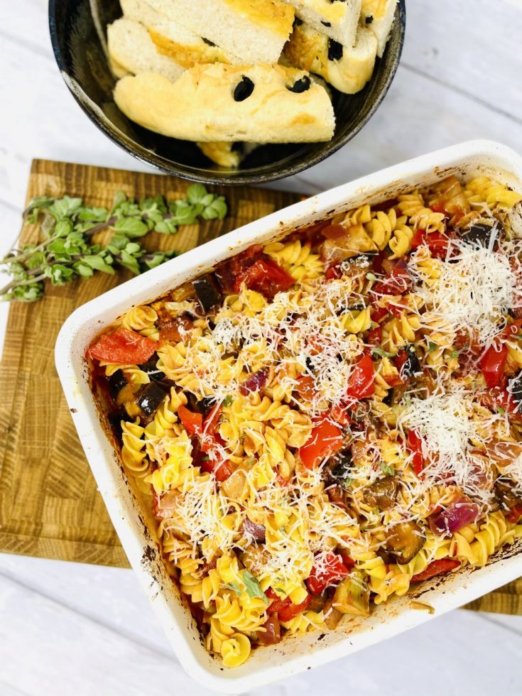 roasted vegetable pasta in a enamel roasting tin, scattered with grated Parmesan cheese. Tray on a wooden chopping board with bowl of homemade focaccia bread and small bunch of fresh oregano