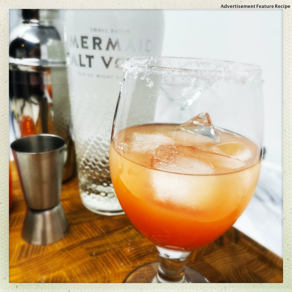 Salty Dog cocktail with grapefruit and ice next to a bottle of Mermaid Salt Vodka and a stainless steel cocktail shaker