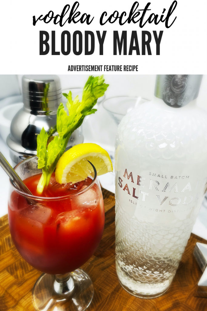 """Bloody Mary cocktail garnished with celery and lemon wedge served in glass next to a bottle of Mermaid Salt Vodka. Text overlay """"vodka cocktail bloody mary - advertisement feature recipe"""""""