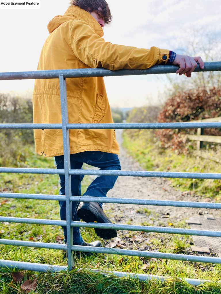 man leaning on a fence taking in the benefits of fresh air as he looks across the countryside