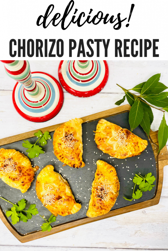 "scattered with smoked paprika and sesame seeds on a black board with flat leaf parsley and bay leaves. Text overlay ""delicious chorizo pasty recipe"""