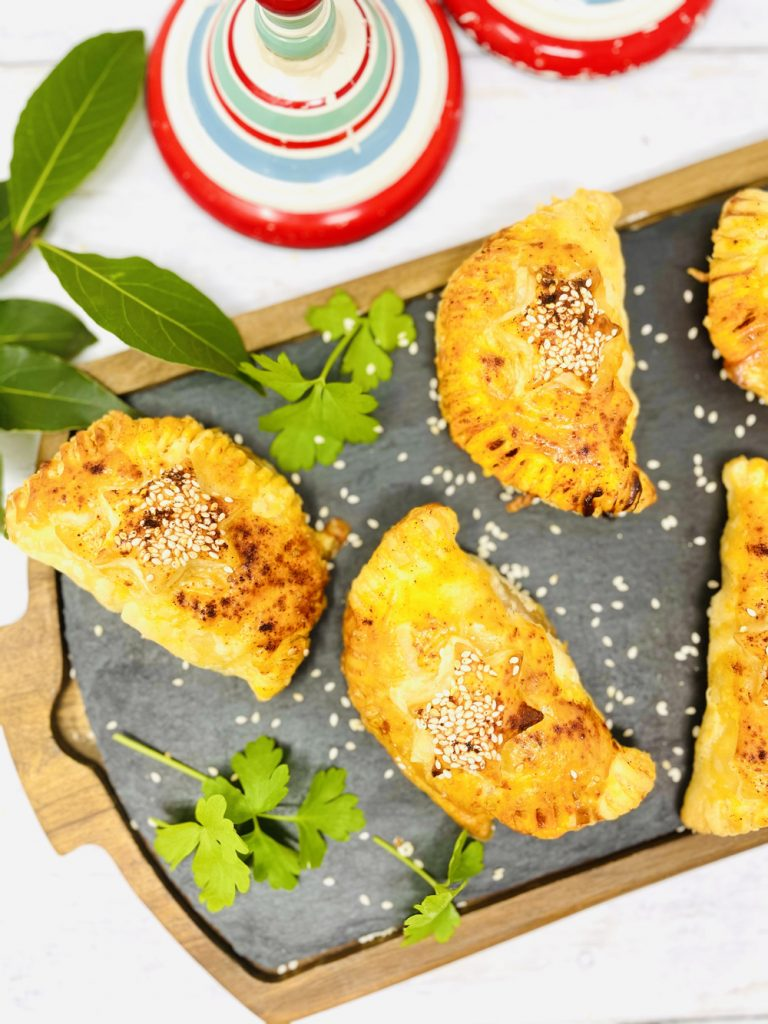 chorizo pasties scattered with smoked paprika and sesame seeds on a black board with flat leaf parsley and bay leaves