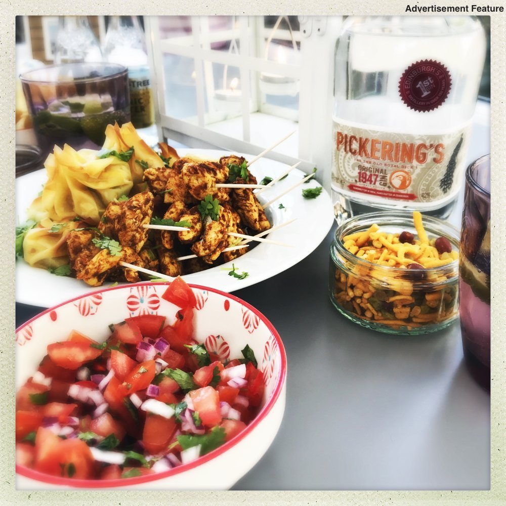 indian snack platter next to a bottle of Pickerings gin