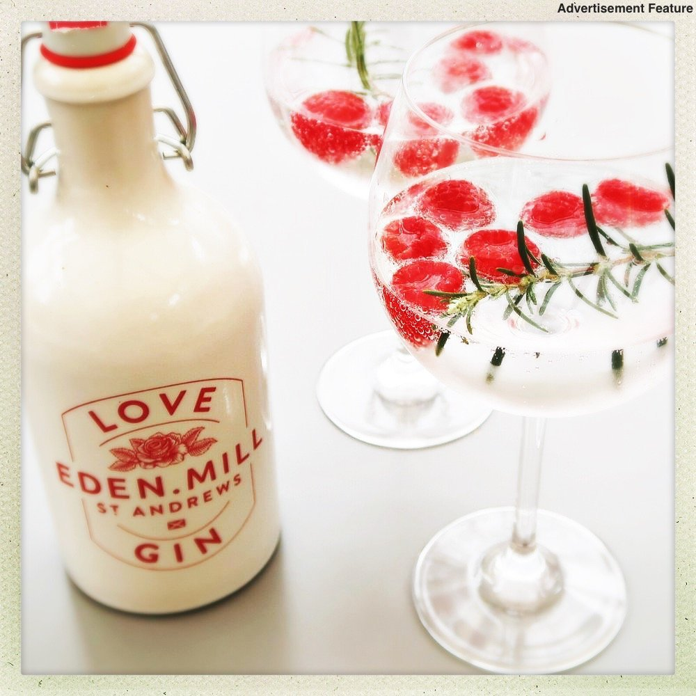 bottle of Eden Mills Love Gin next to two balloon glasses filled with gin, tonic and raspberries with sprig of rosemary