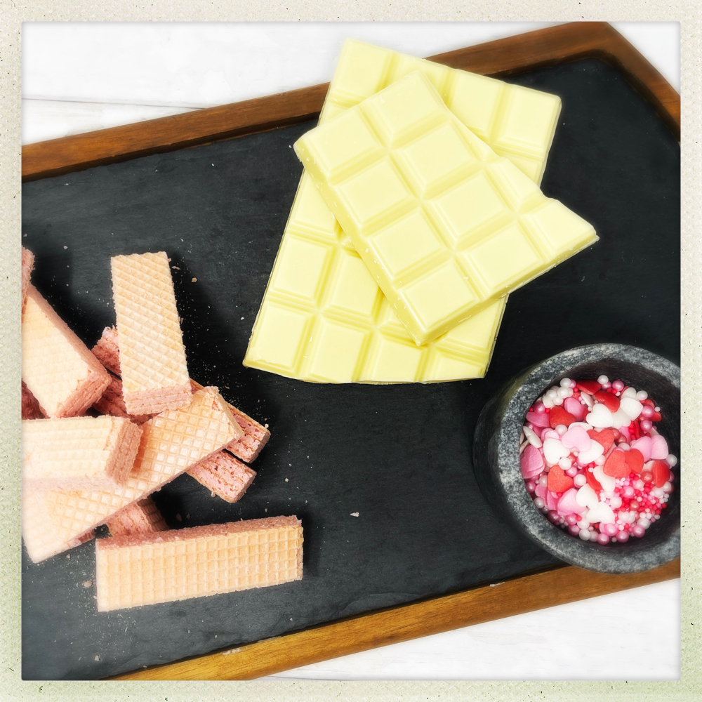 ingredients for pink wafer valentines biscuits with white chocolate and heart sprinkles
