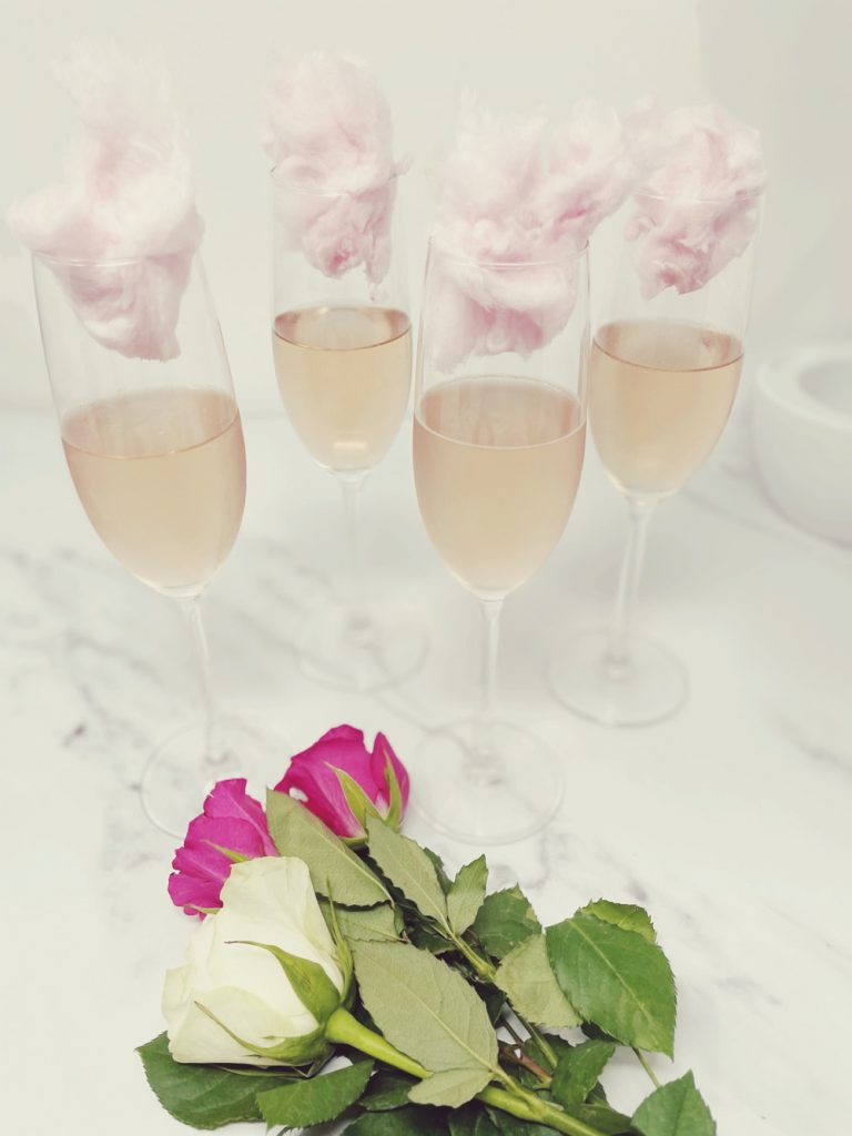 candyfloss cocktail with pink champagne and balls of candy floss  - bunch of roses lies next to glasses