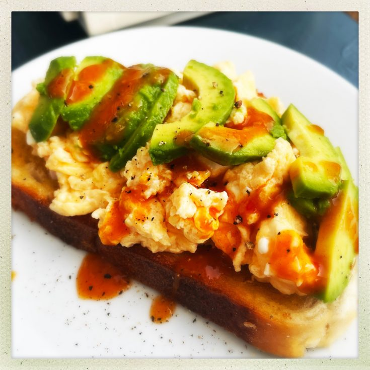 cheesy scrambled eggs with feta and avocado on toast with Nando's chilli sauce