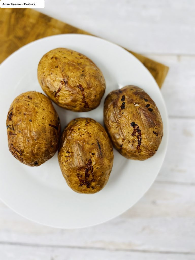 freshly baked jacket potatoes with dark crisp skins and salt
