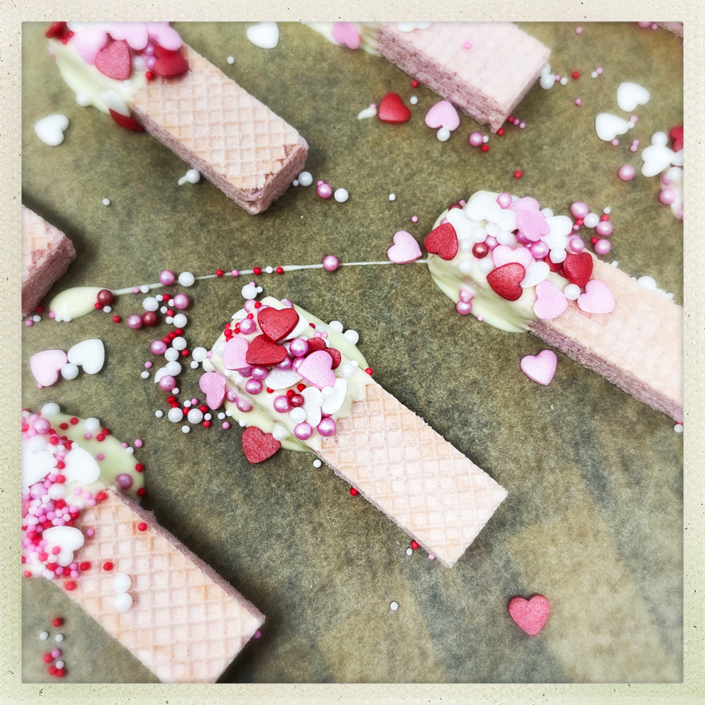 pink wafer biscuits dipped into white chocolate and sprinkled with heart shaped cake sprinkles