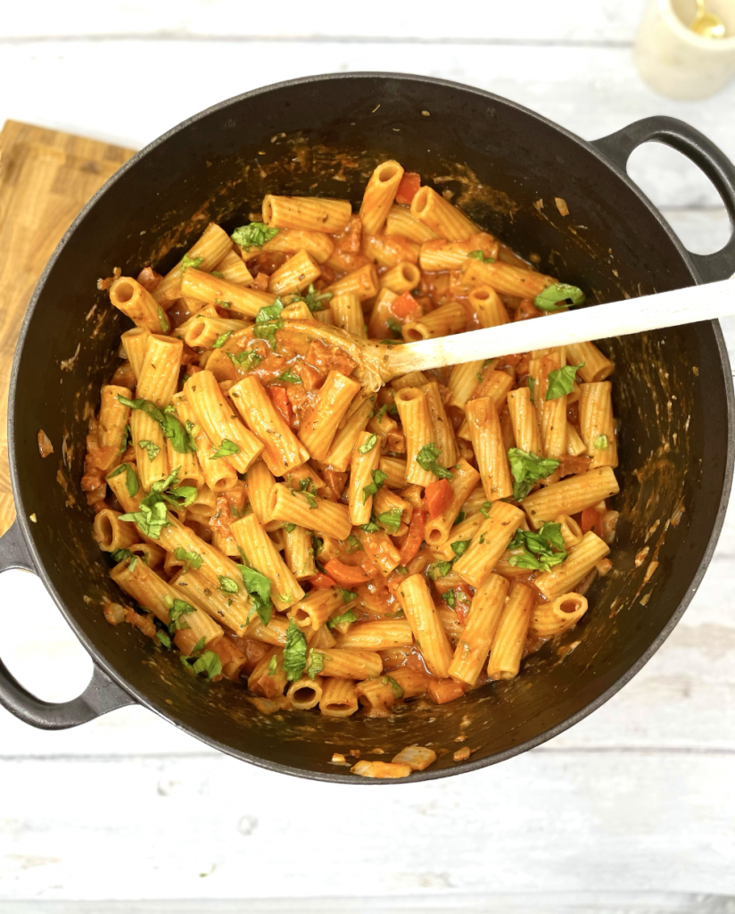 cheesy chorizo pasta in a large black le creuset pan