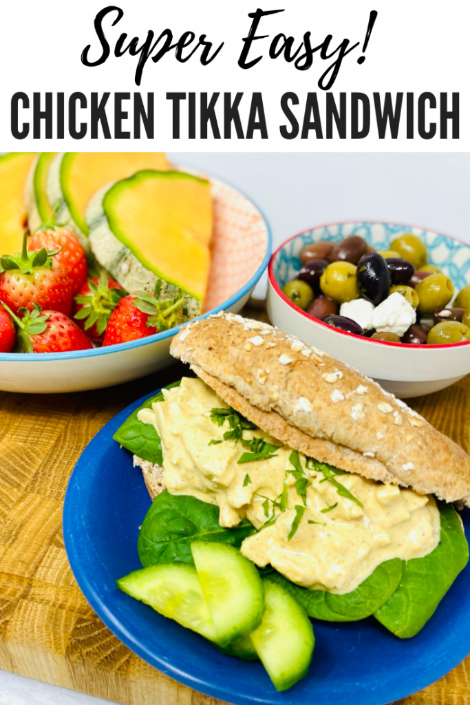 """chicken tikka sandwich made with homemade chicken tikka sandwich filler. A bowl of fruit and bowl of olives are also on the table. Text overlay reads """"super easy chicken tikka sandwich"""""""